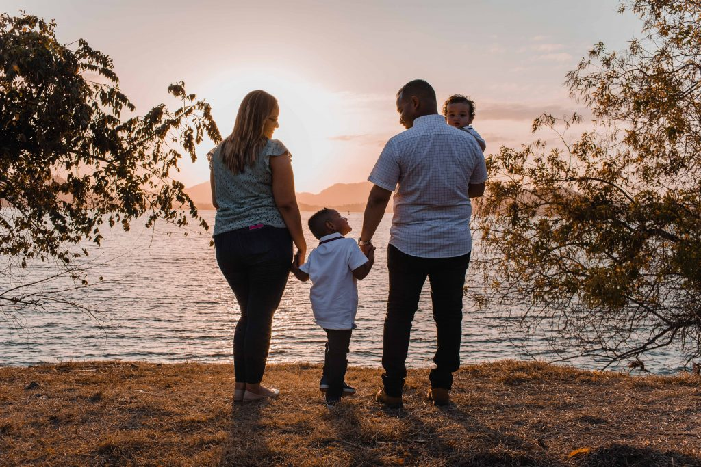 family of four facing a body of water at sunset